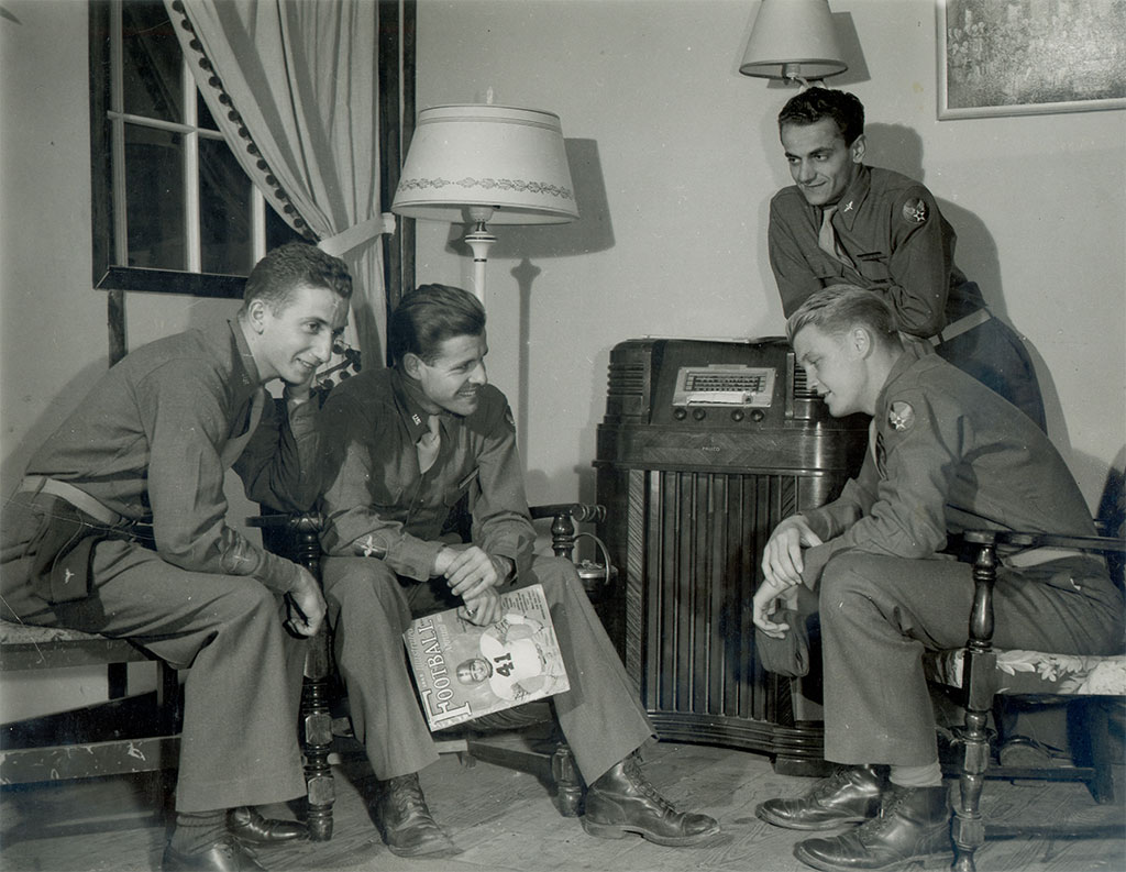 U-M aviation cadets listen to the 1943 Michigan-Ohio State game while stationed at the Army Air Forces Pilot School in Greenwood, Miss. They are, seated from left, Joseph H. Hellman, Norman S. Teahan and James O. Nordlie. Standing is Harold A. Nefe.