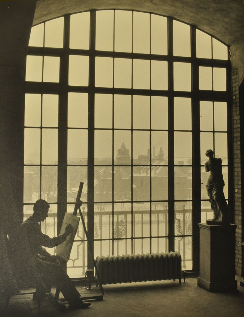 A student draws in the Architecture Building, today's Lorch Hall. The view overlooks South University Avenue and West Engineering Annex, demolished in 1956 for today's Shapiro Undergraduate Library.