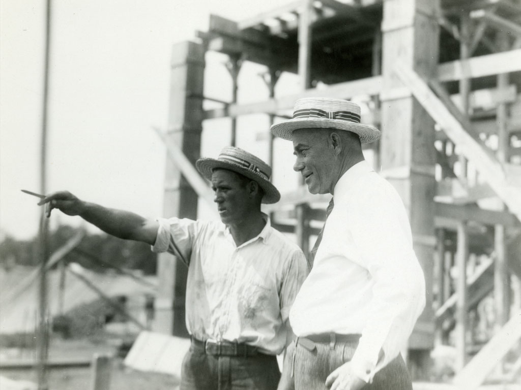 Yost, with a contractor, surveys the construction of his crowning achievement, Michigan Stadium.