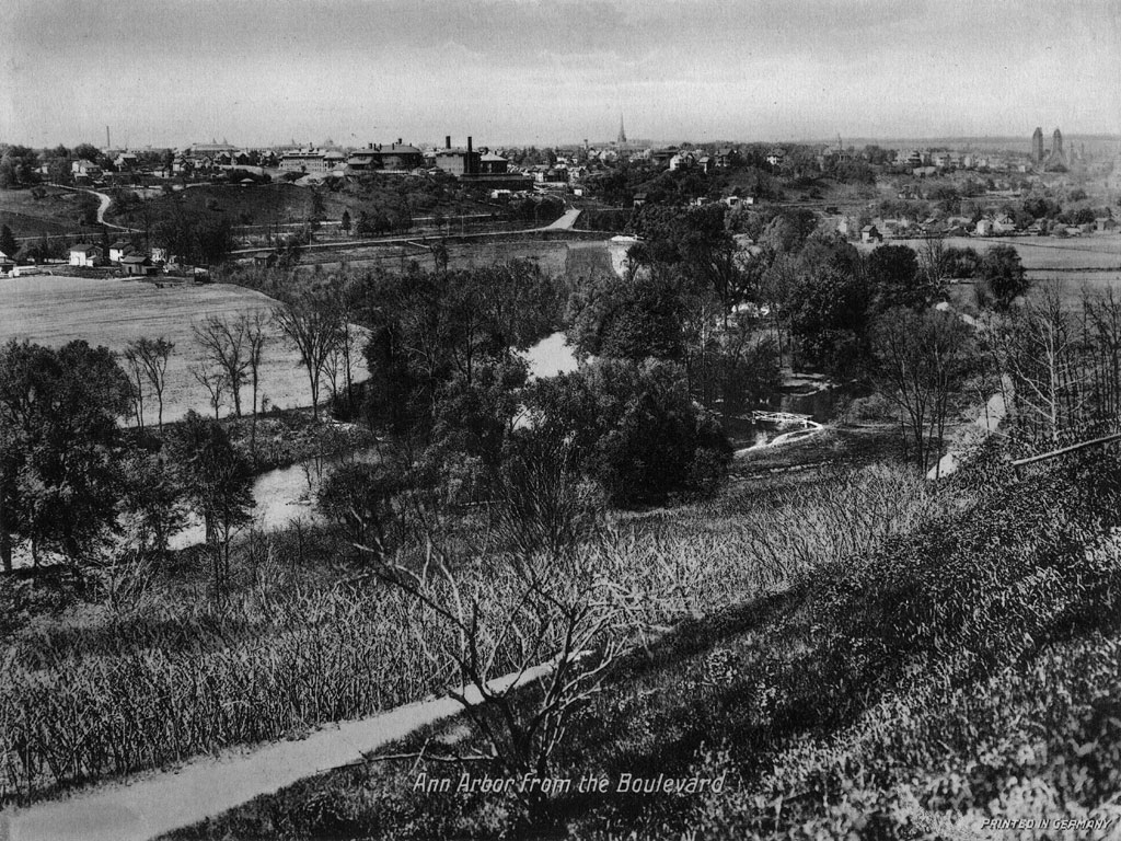 A postcard view of Ann Arbor and the Huron River valley from the summit of the Boulevard, about 1920. The brick-red buildings on the horizon at left are the Catherine Street Hospitals, predecessors of University Hospital (Old Main). The church at far right is St. Thomas the Apostle, on North State Street.