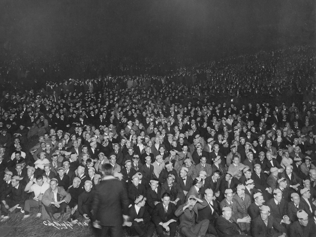 In the second Sleepy Hollow, east of Observatory Street, much of the student body masses for Cap Night, circa 1920. Freshmen are seated with their caps on their heads, awaiting the moment when they will toss their caps on a bonfire.